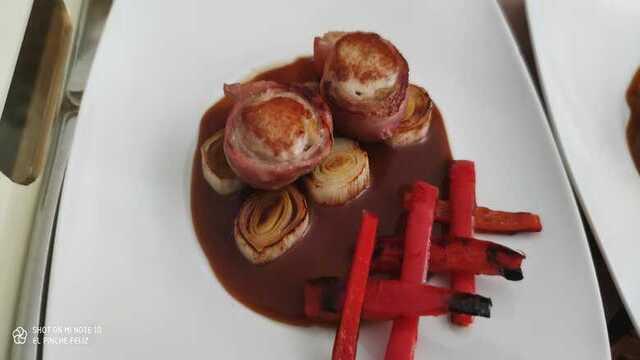 Lomito de conejo albardado con bacon sobre puerros y pimientos braseados